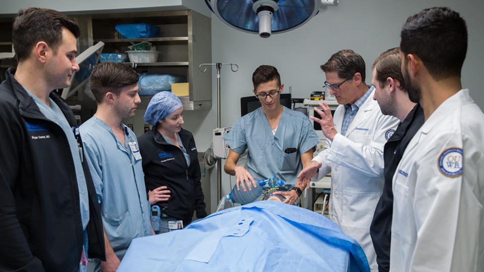 Physician leading a simulated training with other resident physicians or physician anesthesiologists