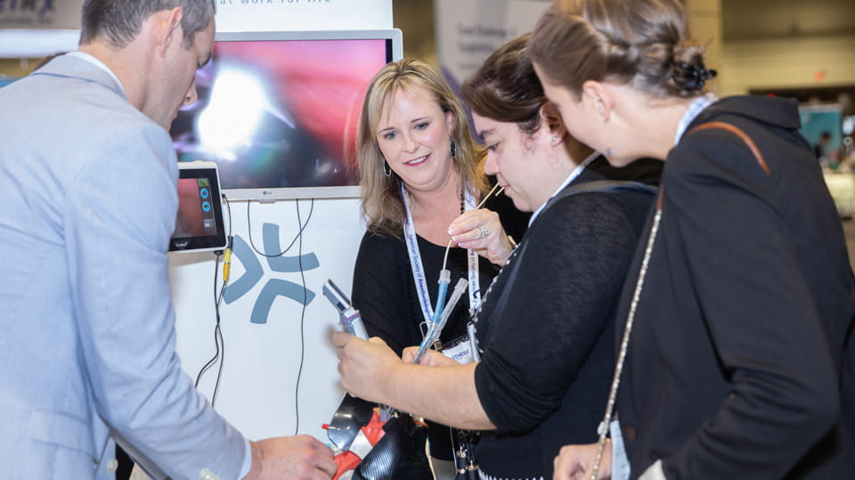 Attendees talk with an Exhibitor and test out products in the exhibit hall.