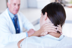 Rear-view of a woman holding her neck in pain talking to her doctor - copyspace