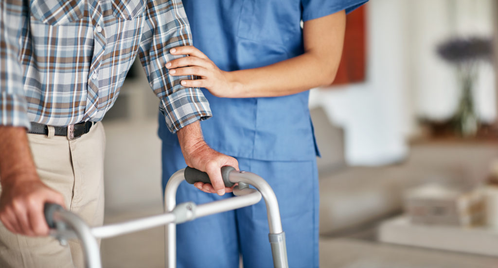 Nurse assisting elderly patient with walker