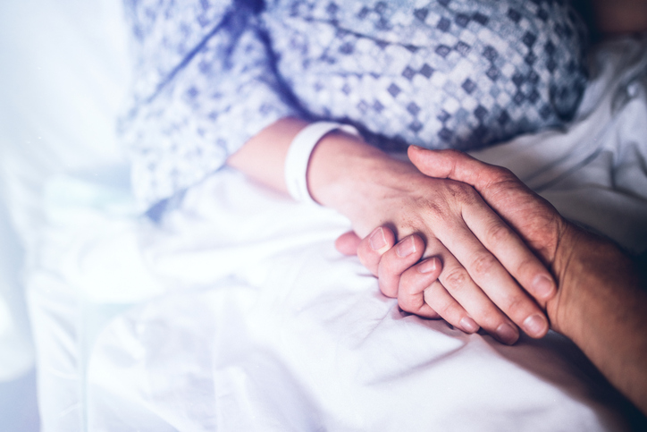 A woman in labor prepares to give birth in a clean white hospital setting, holding the hand of her husband or partner. Detail shot of their hands being held on the white hospital bed linens. A depiction of love and support during pregnancy or any hospital stay. Horizontal image with copy space.