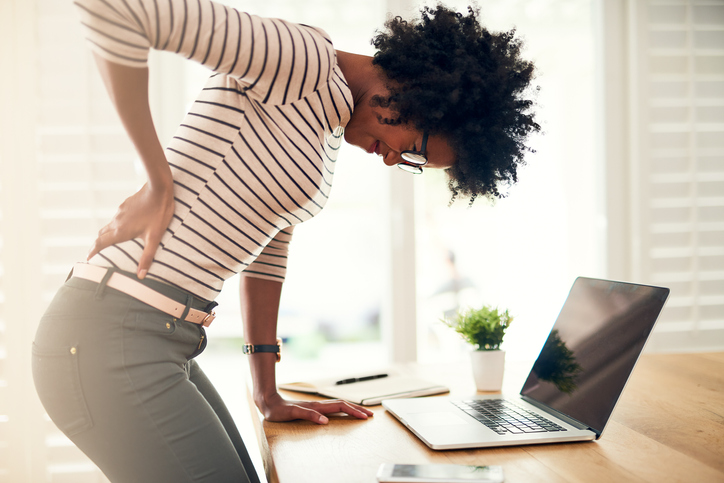 Cropped shot of a young woman holding her sore back while getting up from her desk at home