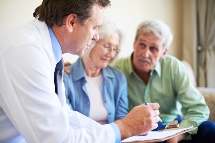 A mature doctor explaining the details of a checkup to a senior couple