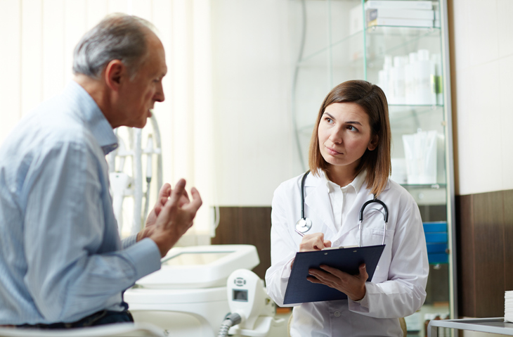 Senior patient explaining his problem to doctor during appointment