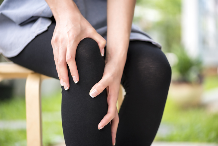 Health care concept, Hands suffering from pain in knee