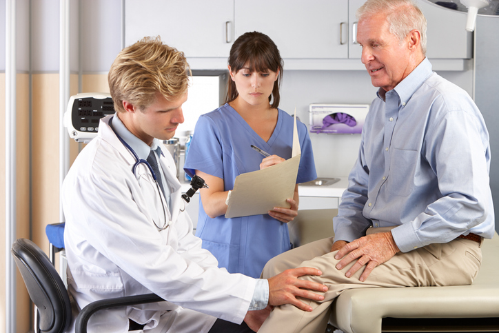 Male Doctor Examining Male Patient With Knee Pain