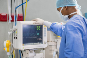 Cardiac Anesthesiologist monitoring patient during heart surgery